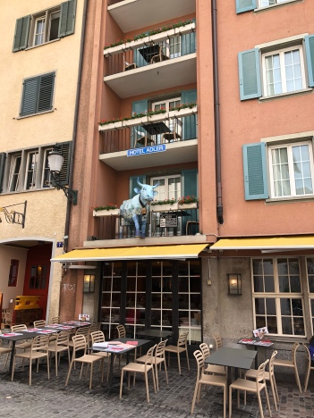 A hotel in Zurich with a cow protruding from a balcony